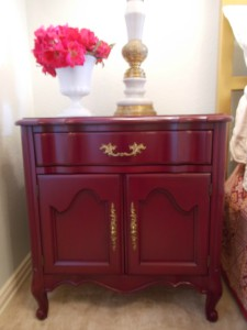 Updated bedside table in a fresh cranberry color with newly gold rub-n-buffed hardware.