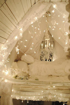 All white bedding with canopy and lights.